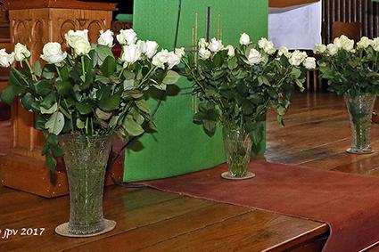 Kaarsjes en witte rozen voor overleden vrienden